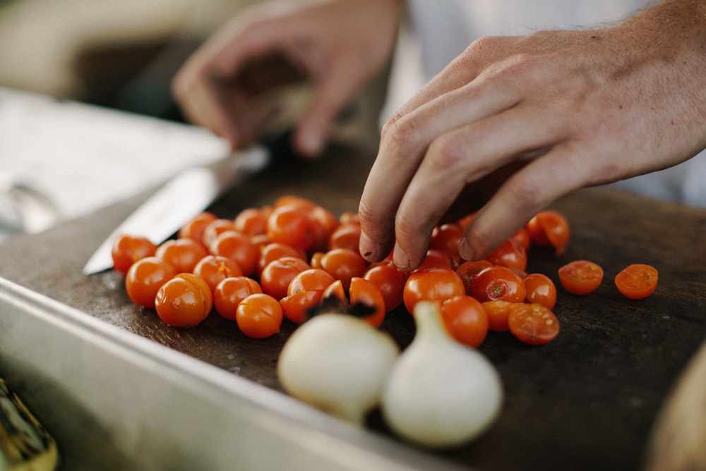 person slicing cherry tomatoes