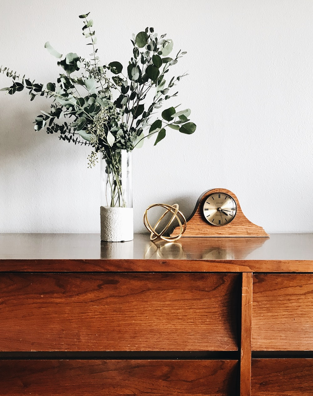 brown wooden framed analog mantle clock near gray petaled flower centerpiece
