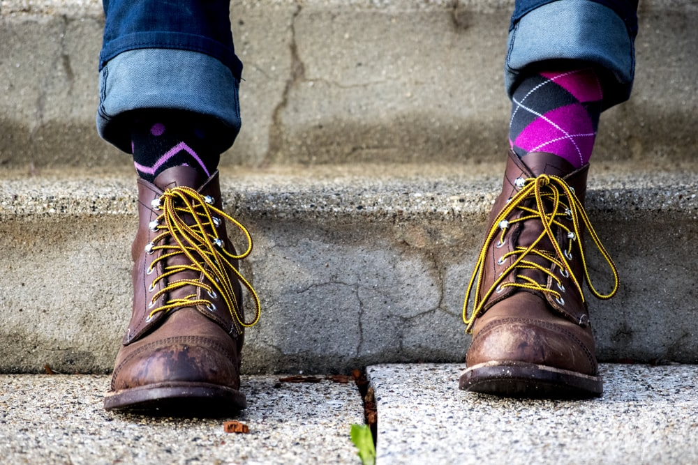 person in brown suede boots and pink socks