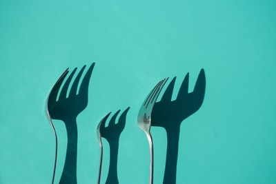 three gray metal forks casting shadow on green surface