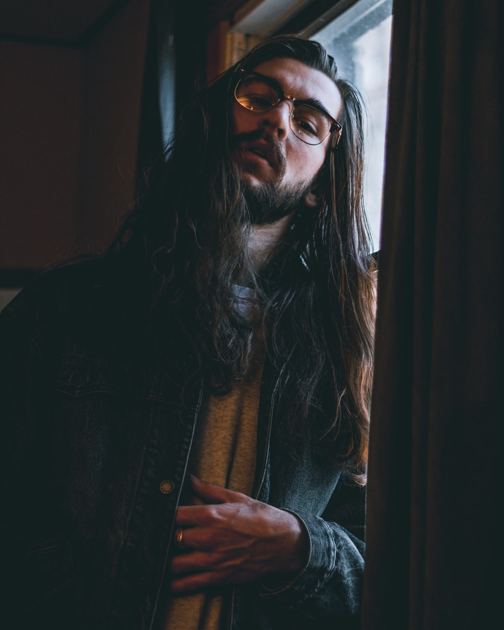 long haired man wearing eyeglasses and blue denim jacket leaning on window