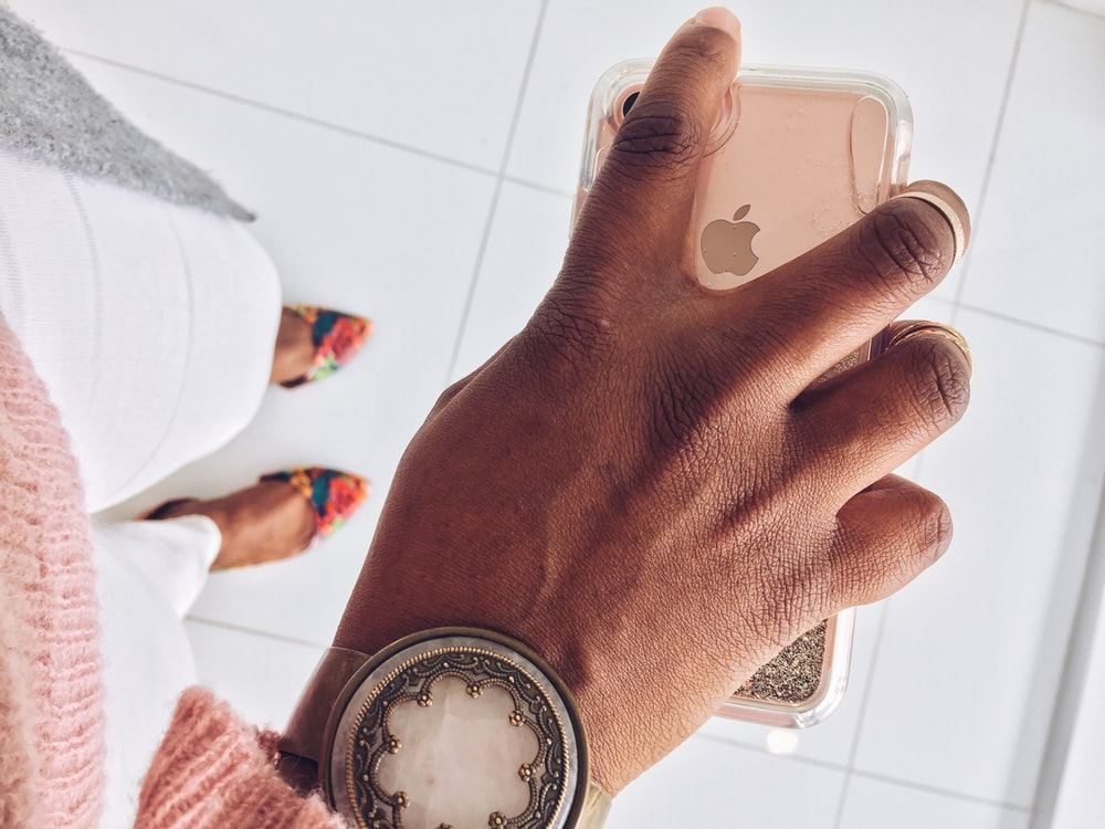 person holding rose gold iPhone