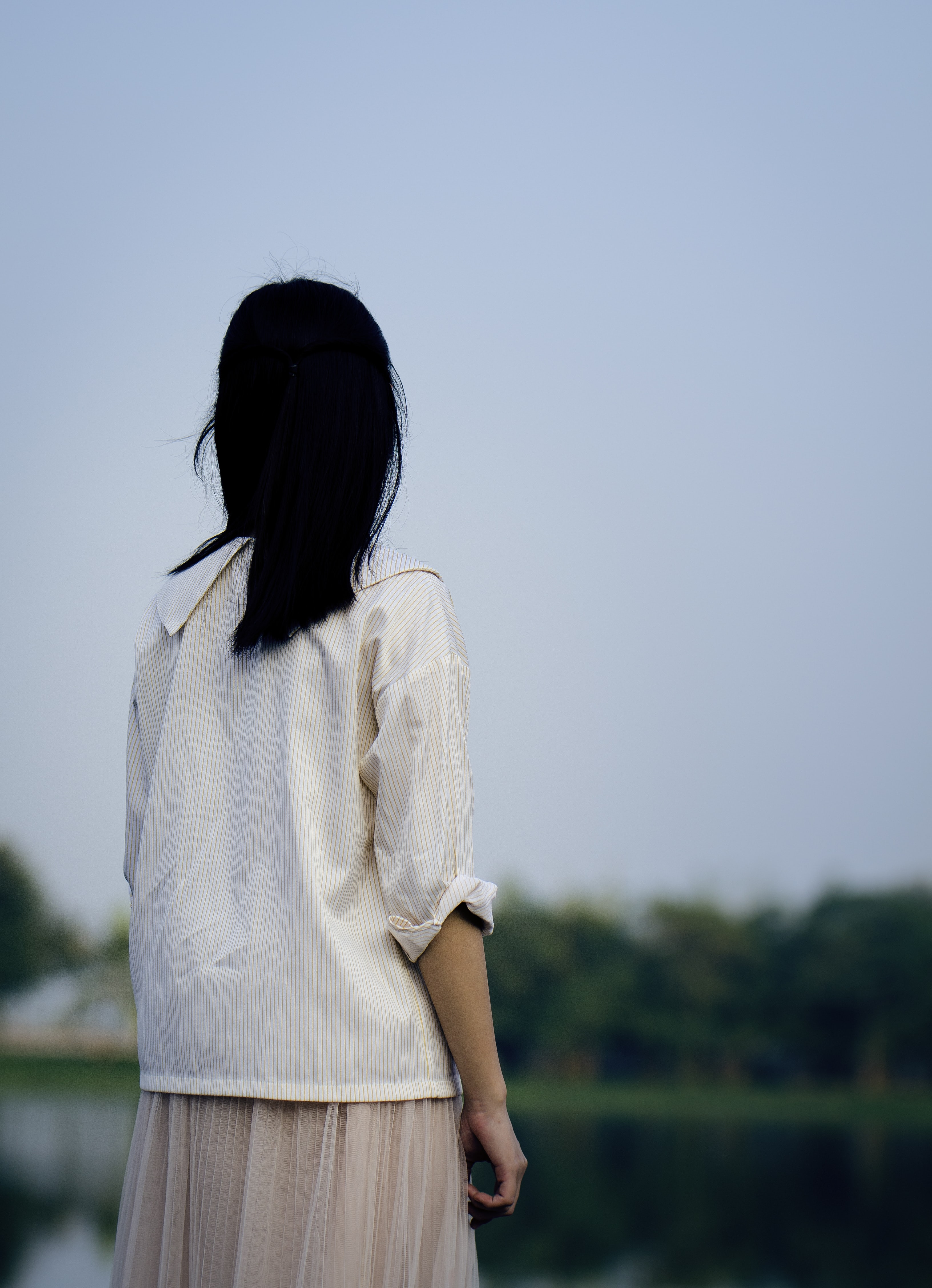 woman wearing white shirt standing under blue sky during daytime photography