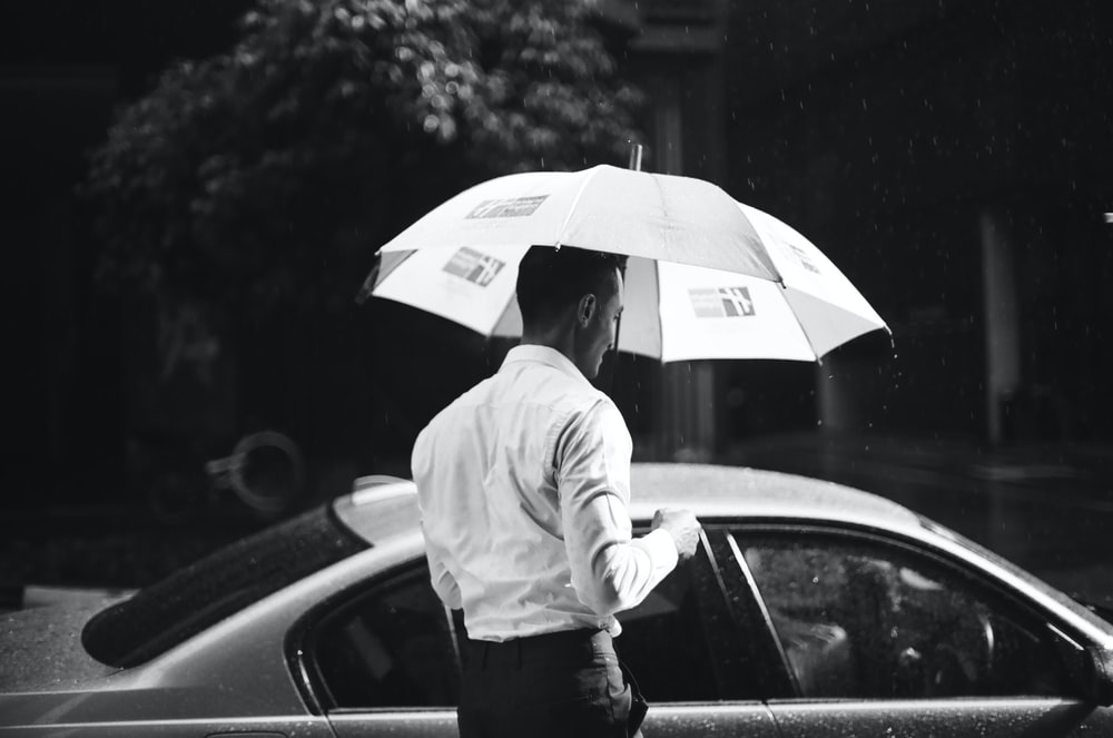 grayscale photography of man holding umbrella in front of sedan