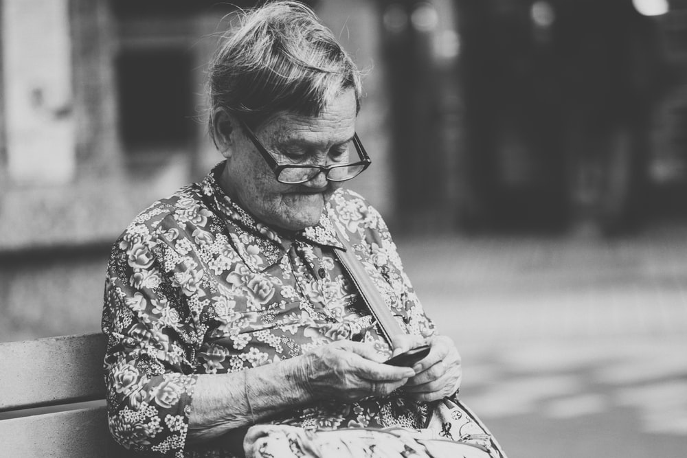 selective focus grayscale photography of woman using phone while sitting at bench