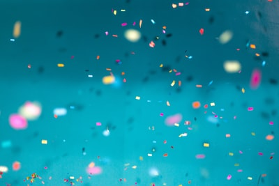 selective focus photography of multicolored confetti lot blue zoom background