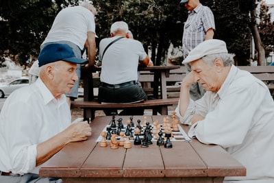 two men playing chess old teams background