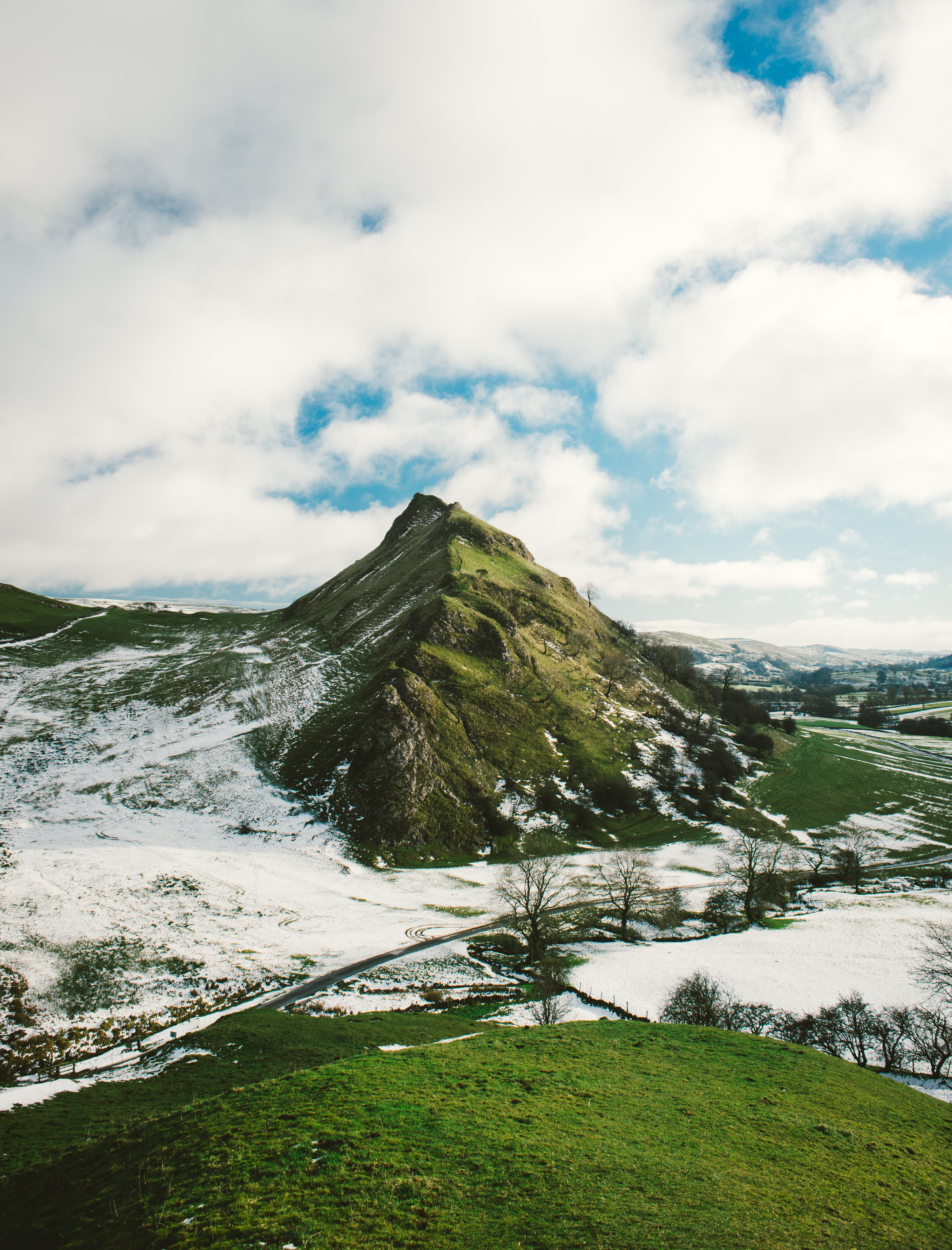 snowy hill under white clouds at daytime