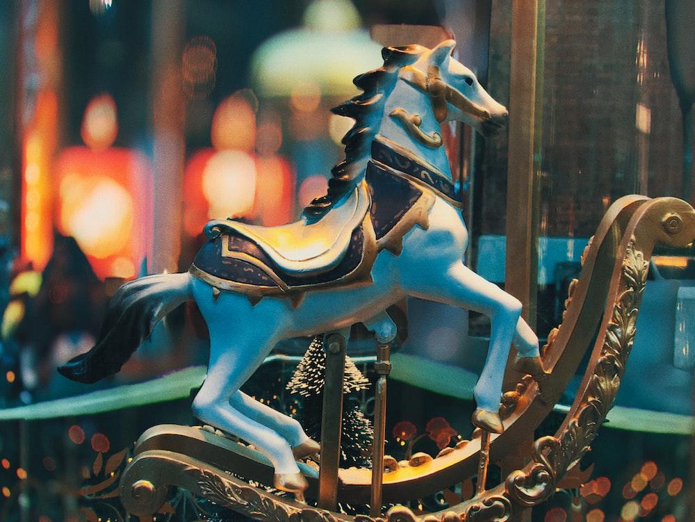 selective focus photo of blue horse carousel
