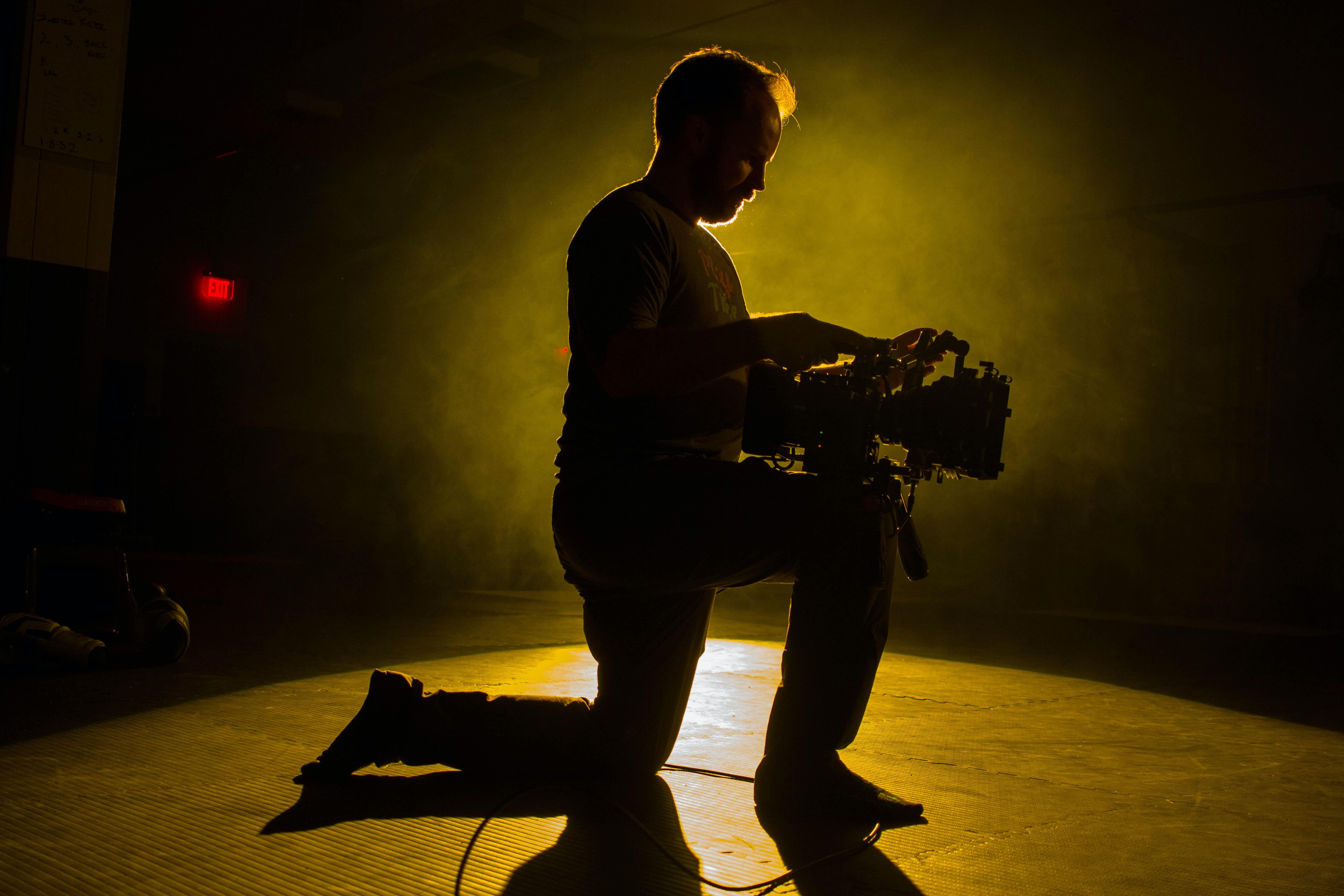 person kneeling while holding camcorder inside dark room