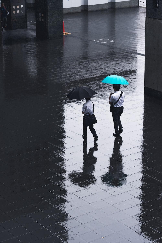 two men walking on road holding umbrellas during rainy time