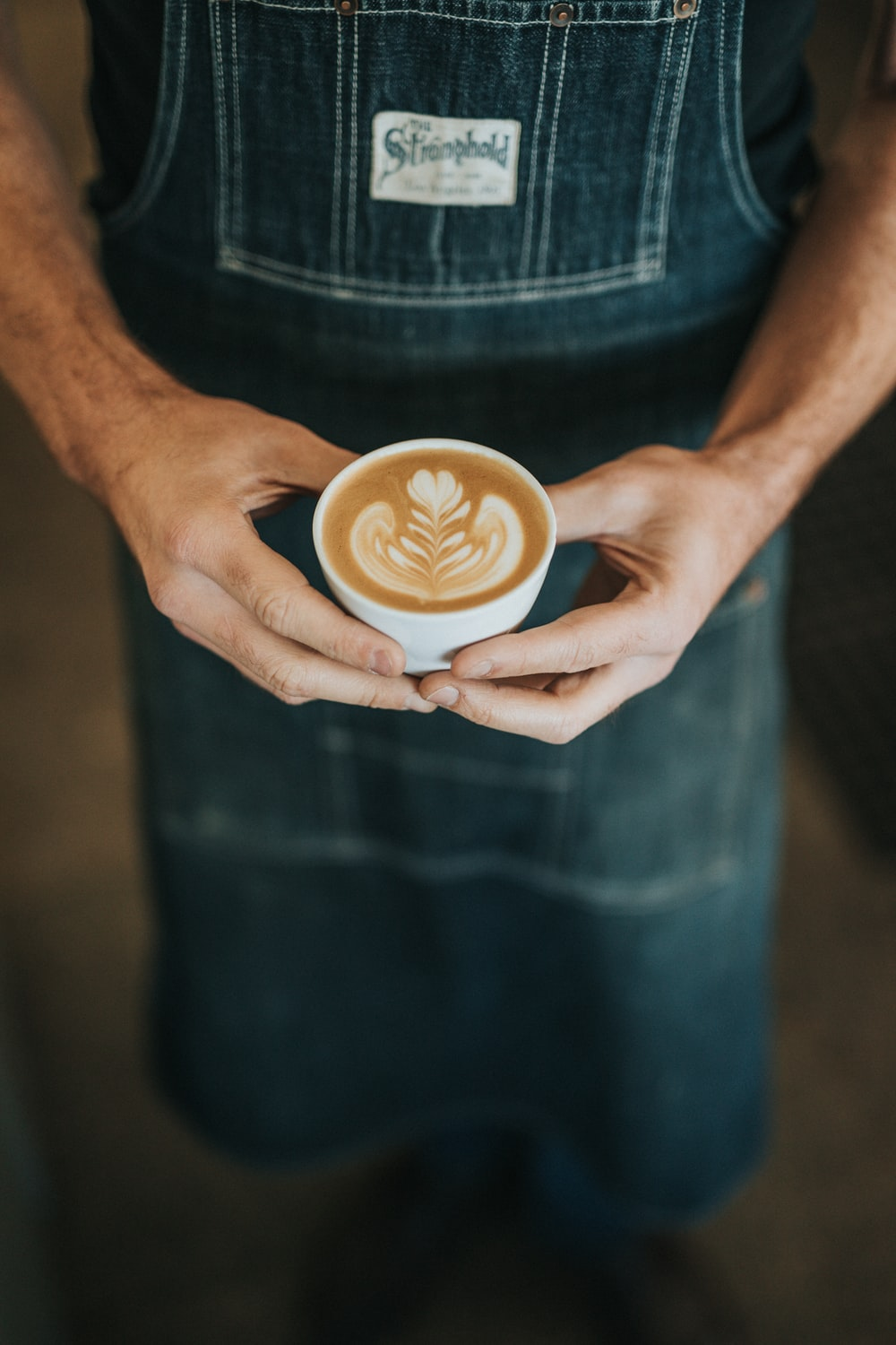 person holding cup of coffee latte