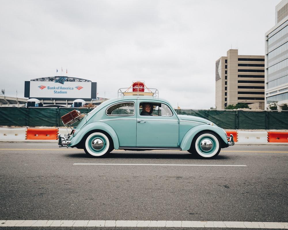 teal Volkswagen Beetle car on road