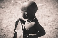 grayscale focus photo of children holding tire