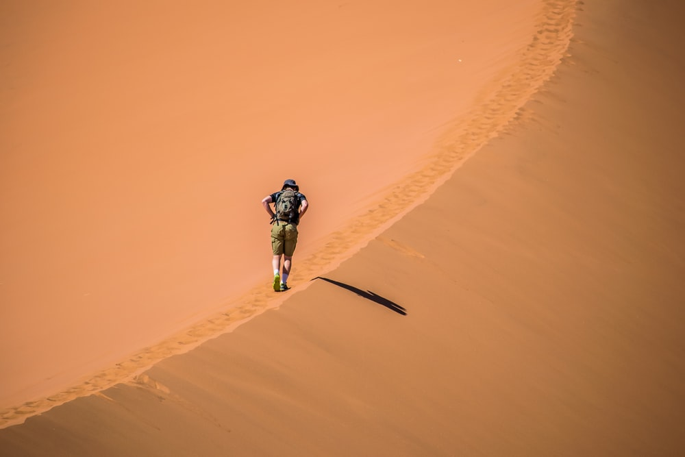 person walking on sand cliff