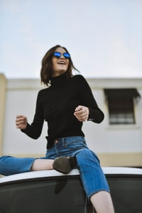 woman wearing black high-neck long-sleeved top while sitting on top of vehicle