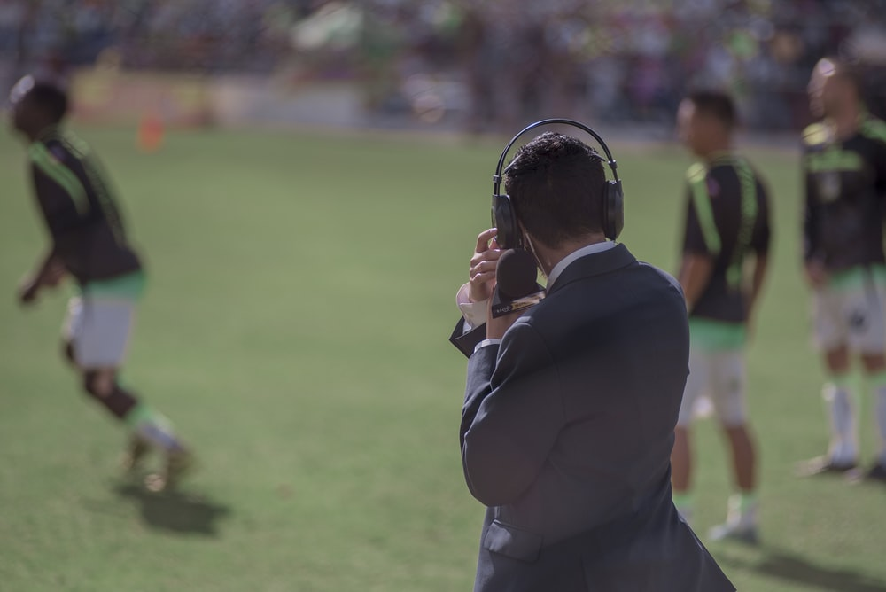 selective focus photography of man using headphones near athletes