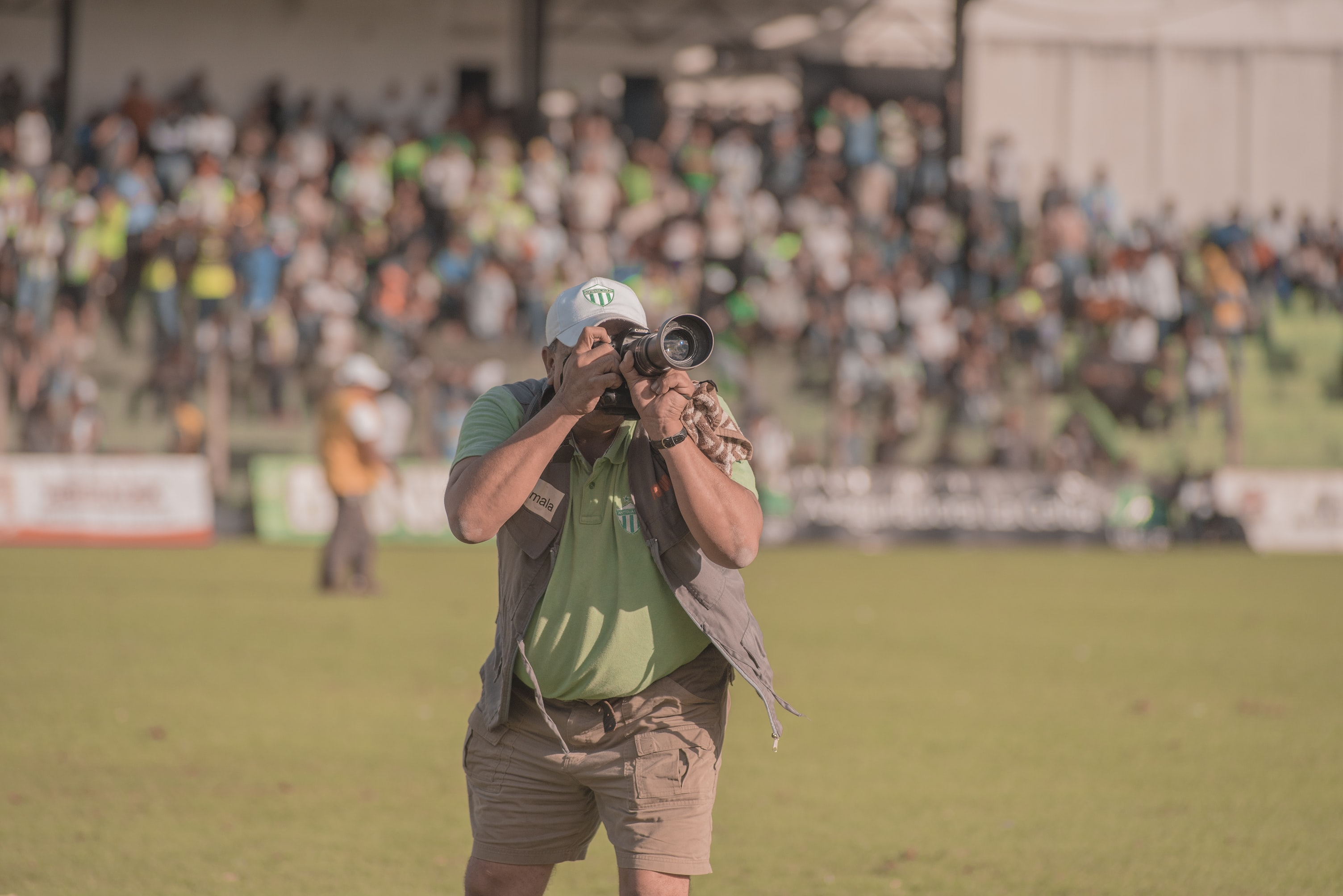 man holding camera near sports field
