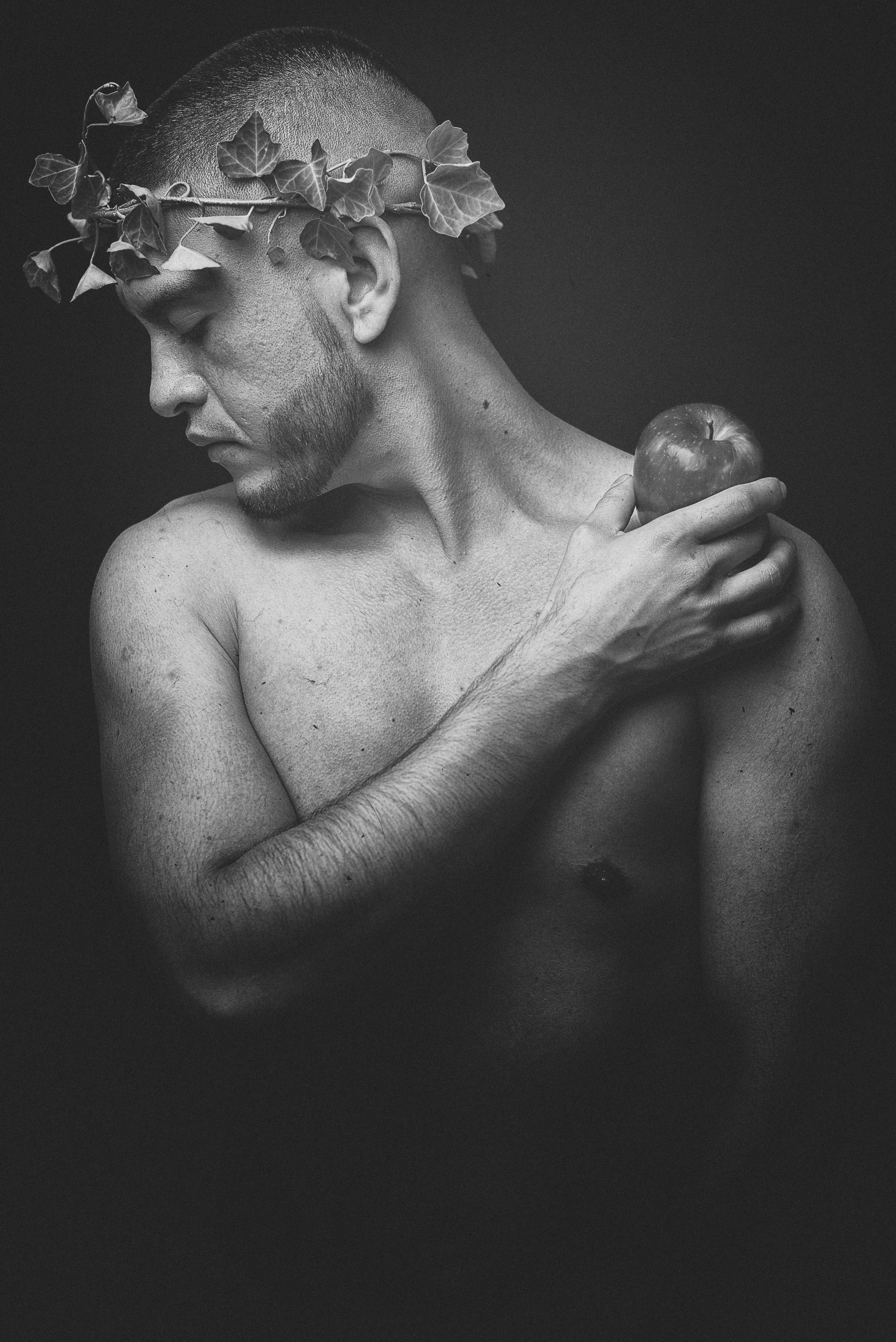 grayscale photo of man holding apple fruit