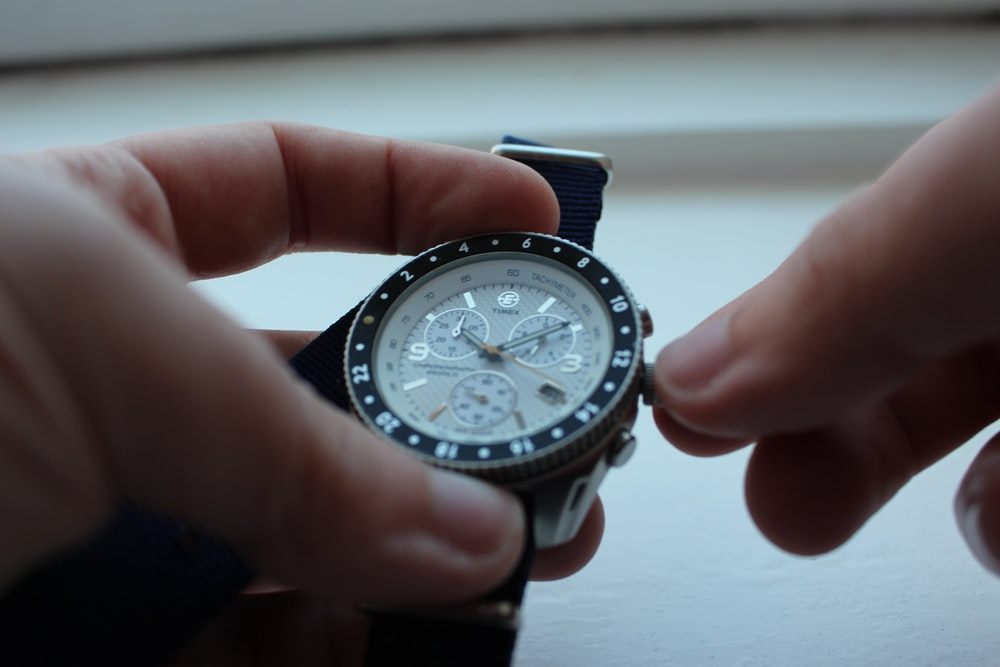person setting the chronograph watch