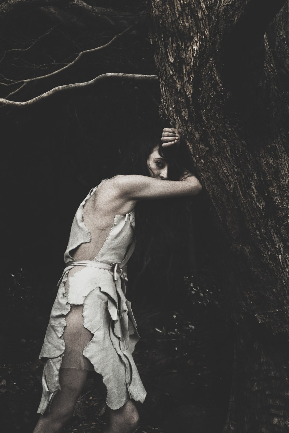 black haired woman leaning on tree trunk