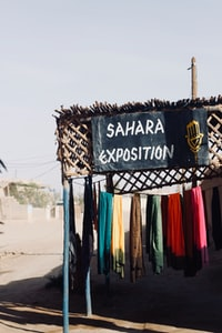 sahara exposition signage near assorted-color apparel on clothesline during daytime