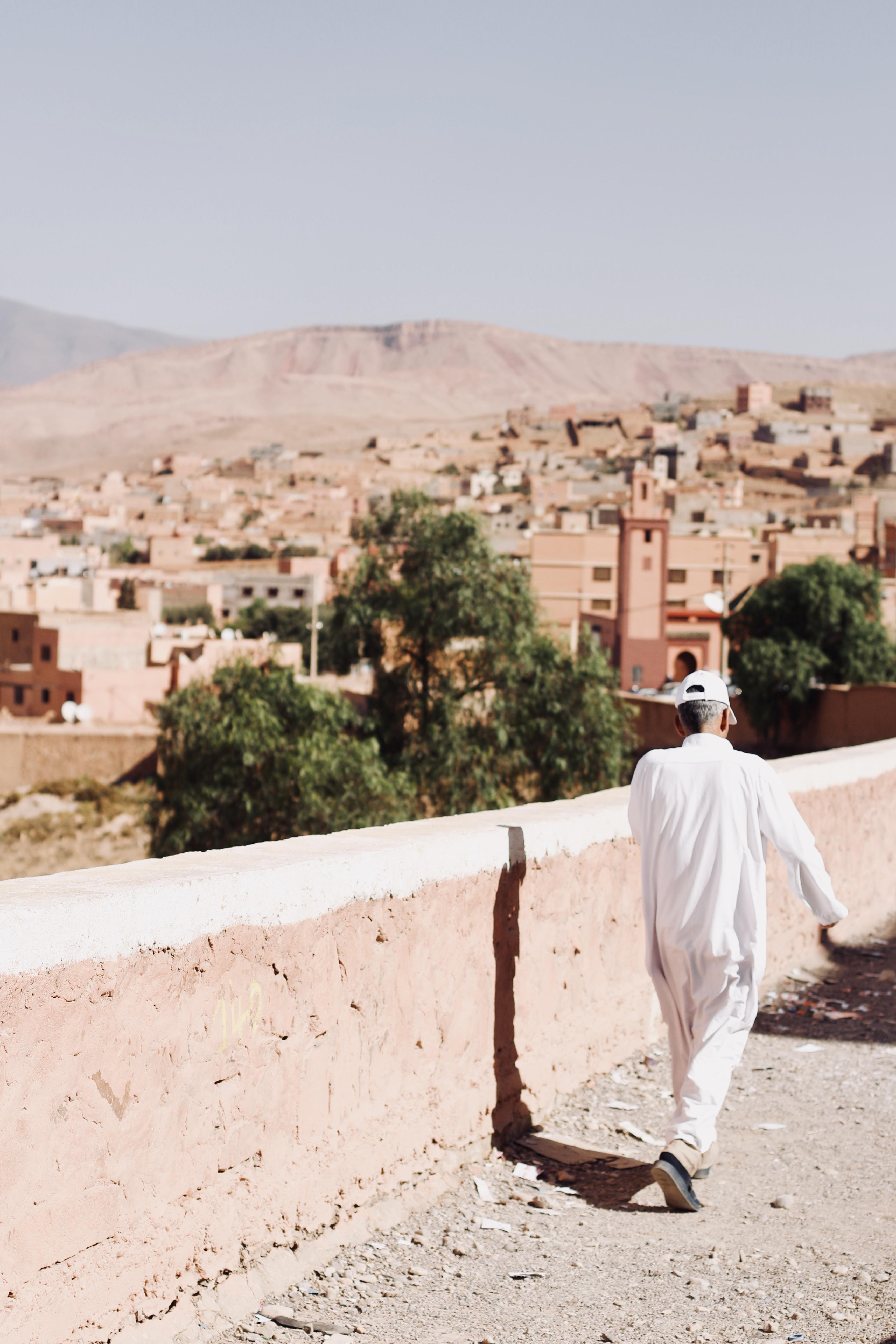 man walking beside white concrete wall