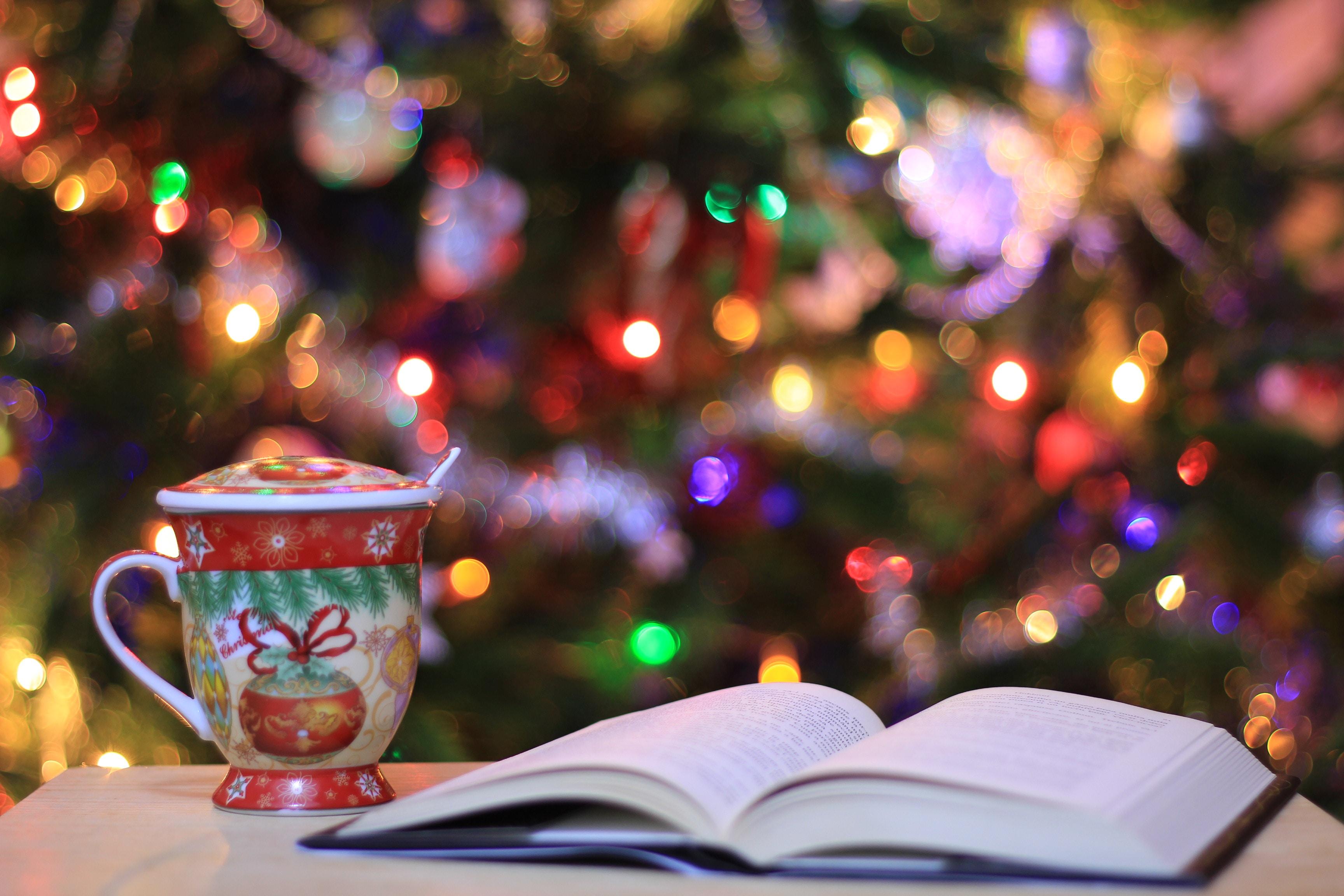 red and green ceramic mug beside book