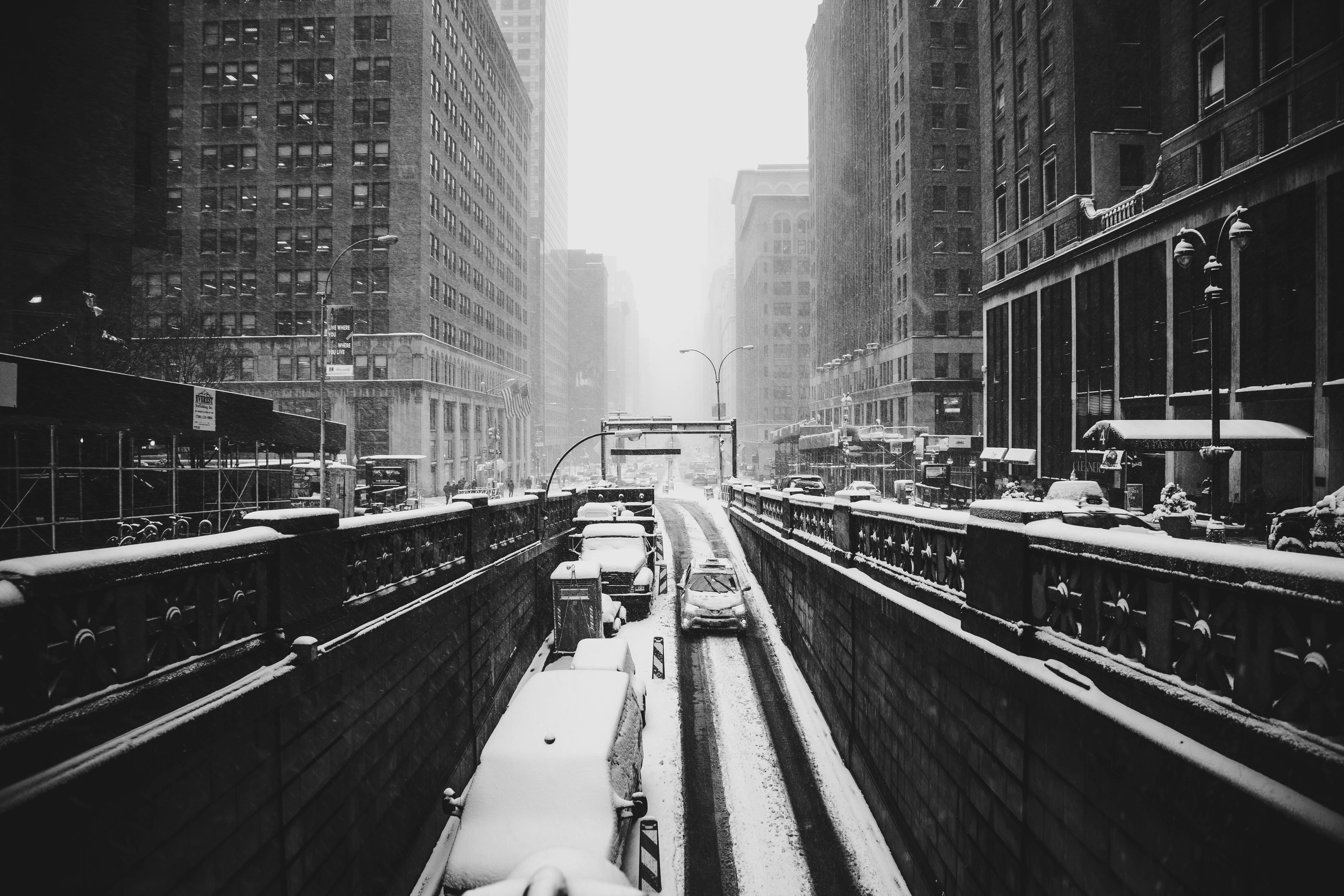 grayscale photograph of road covered by snow