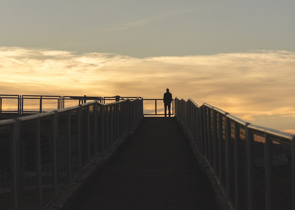 silhouette photography of man standing on corner of bridge