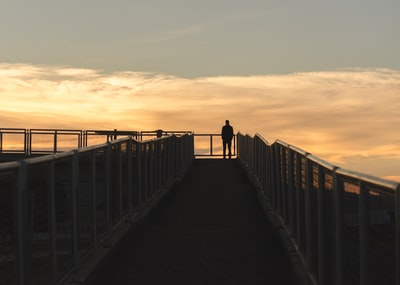 silhouette photography of man standing on corner of bridge