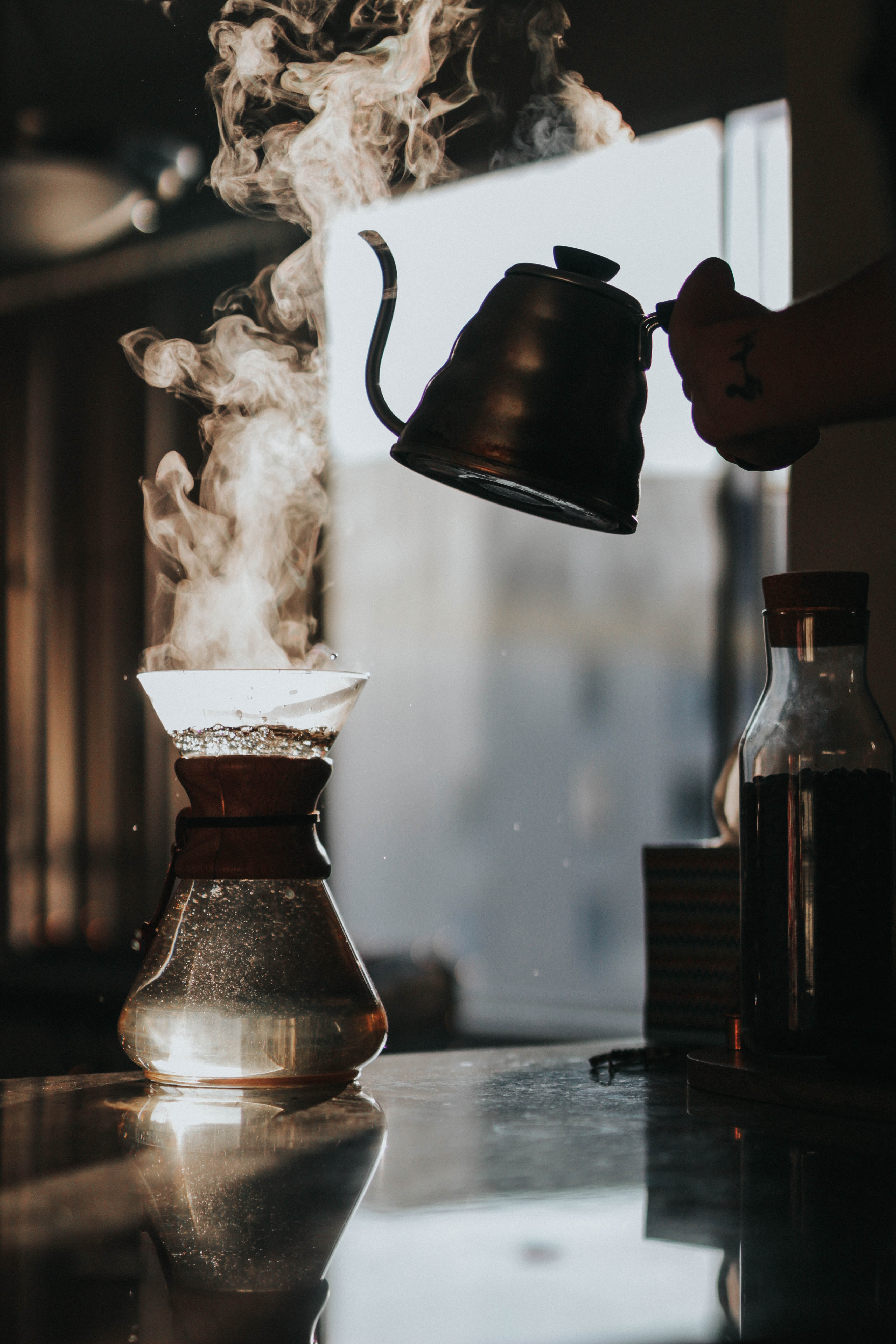 person holding teapot with boiled water