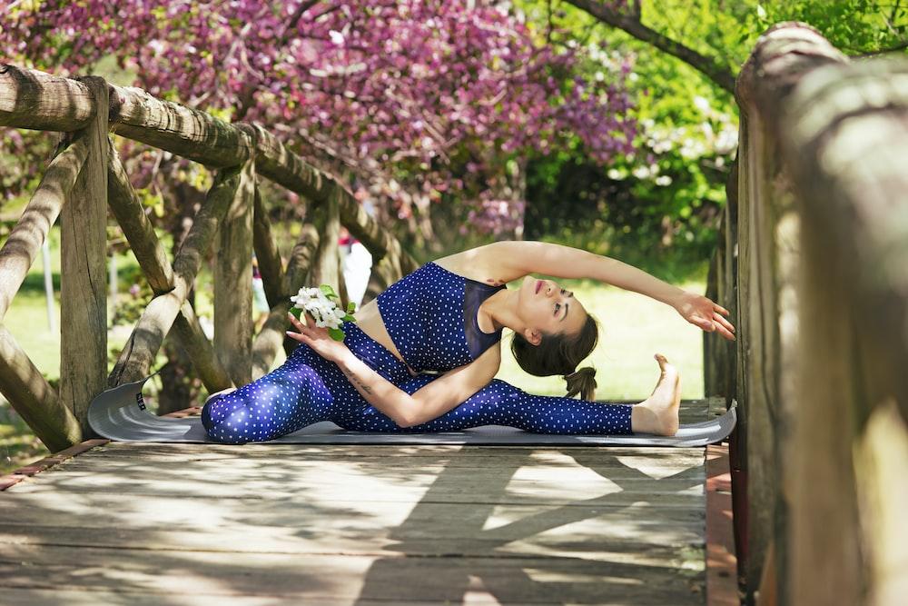 woman doing yoga on brown wooden bridge