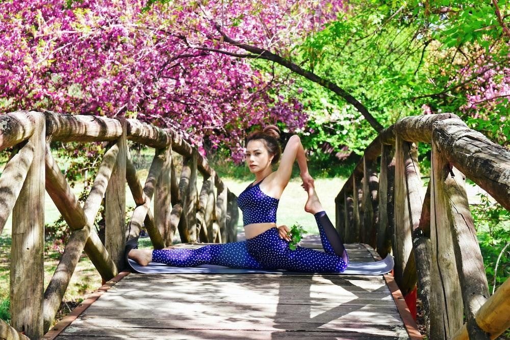 昼間にピンクの花びらの花の木の近くの木の橋で分割をしている女性