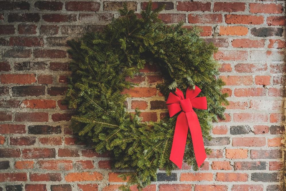 green wreath hang on wall brick