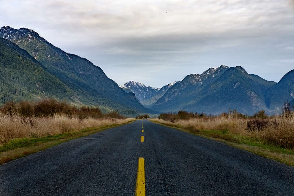 road near mountains under gray sky