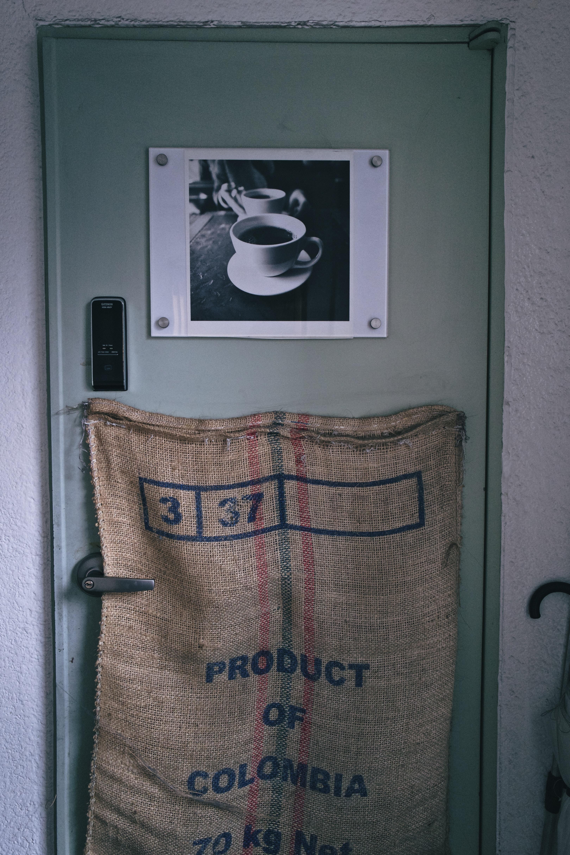 beige and black sack hanging on door