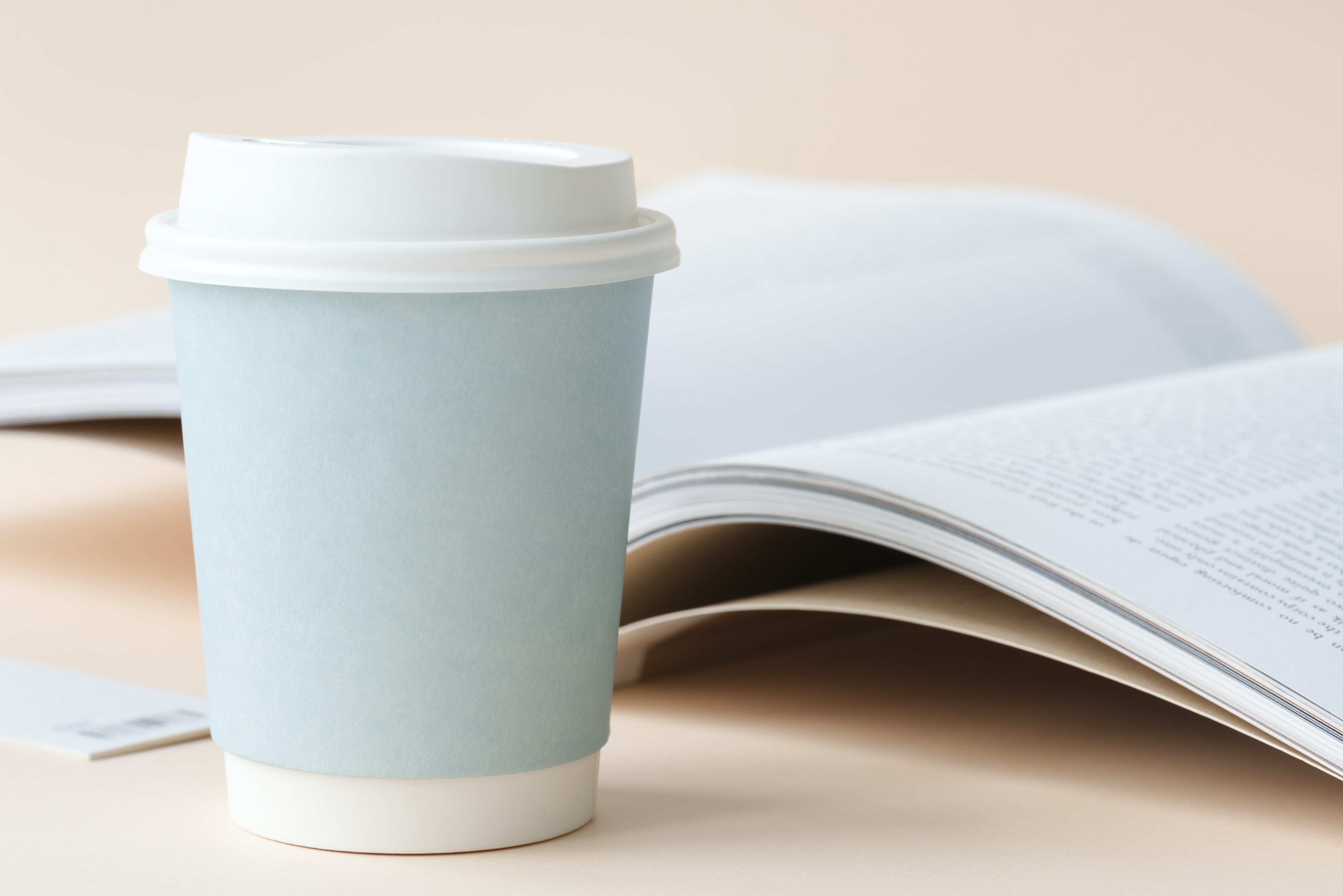 disposable cup near book