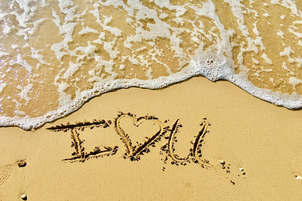 aerial photo of I love you text on sand at the seashore