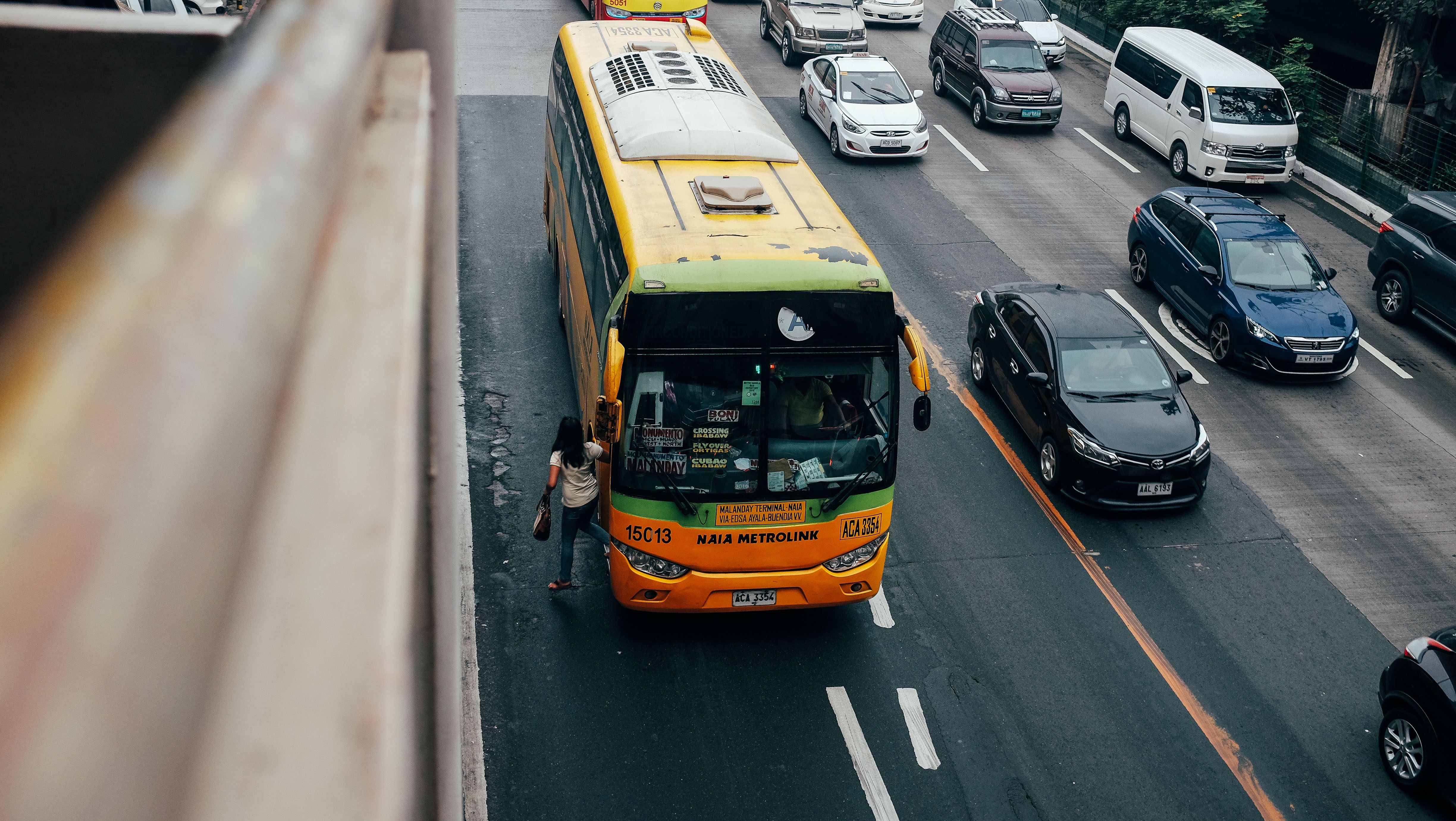 orange and yellow bus on road beside brown building at daytime