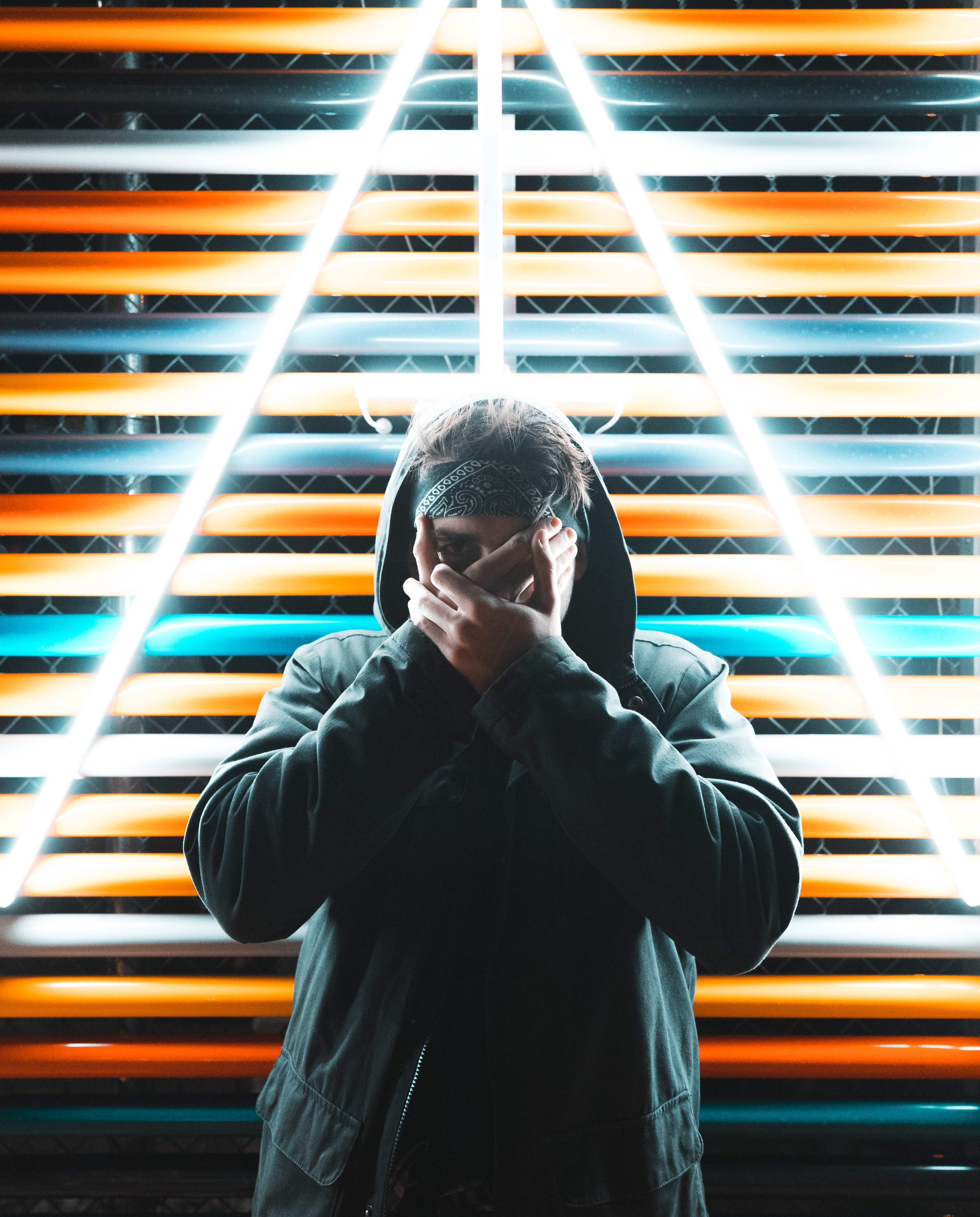 man in black coat standing in front of neon signage
