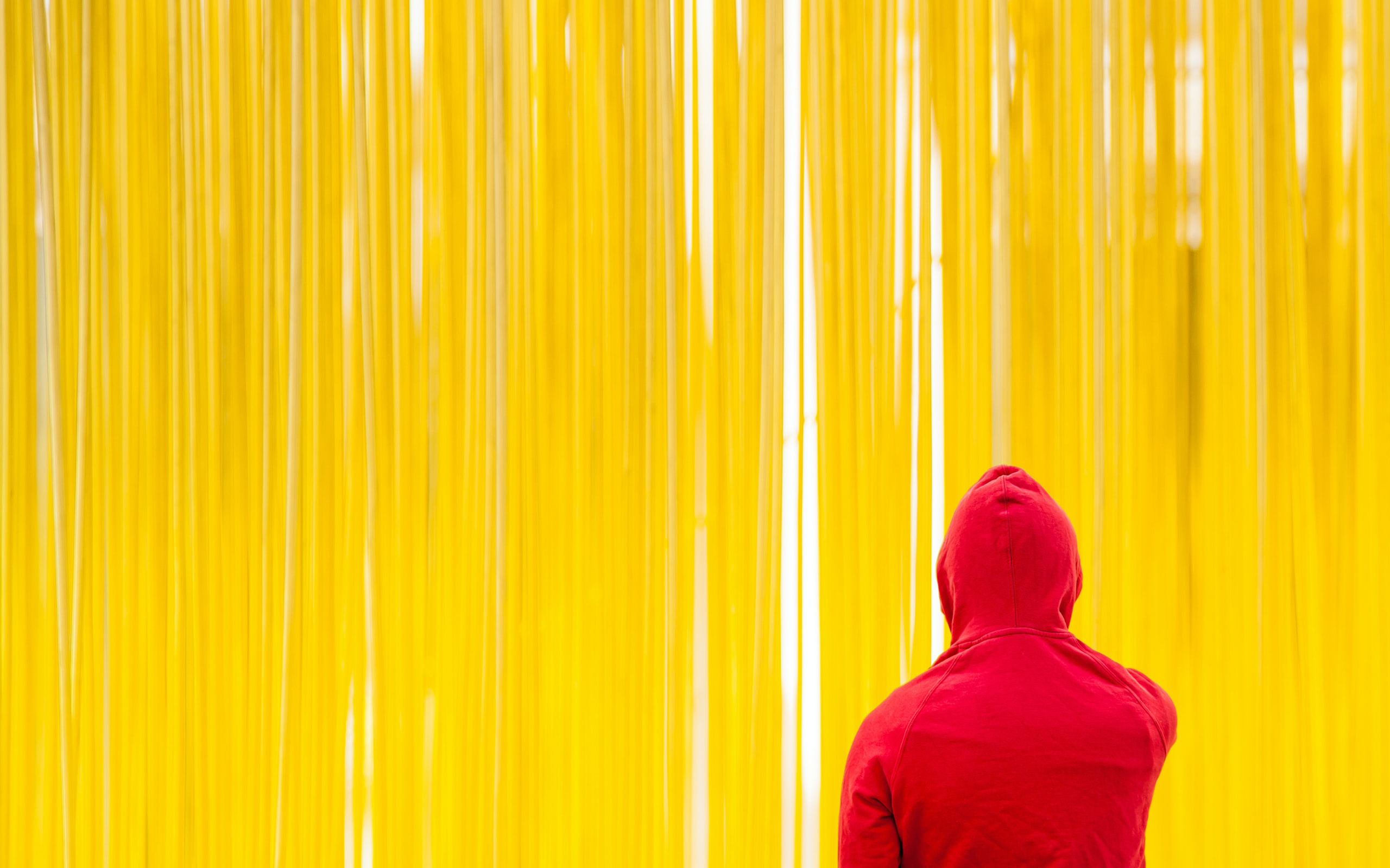 person standing in front of yellow strings