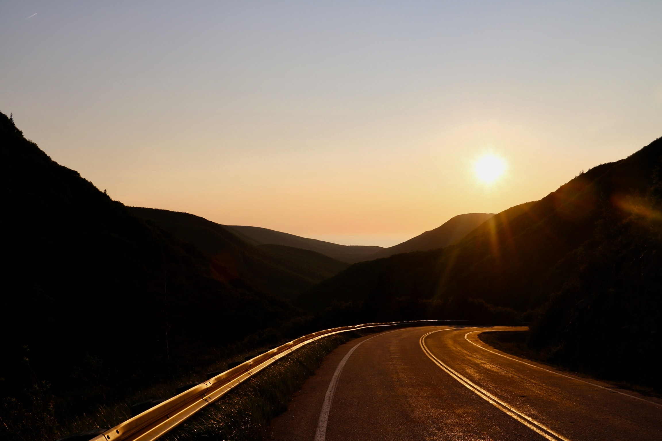 road between mountains during sunset