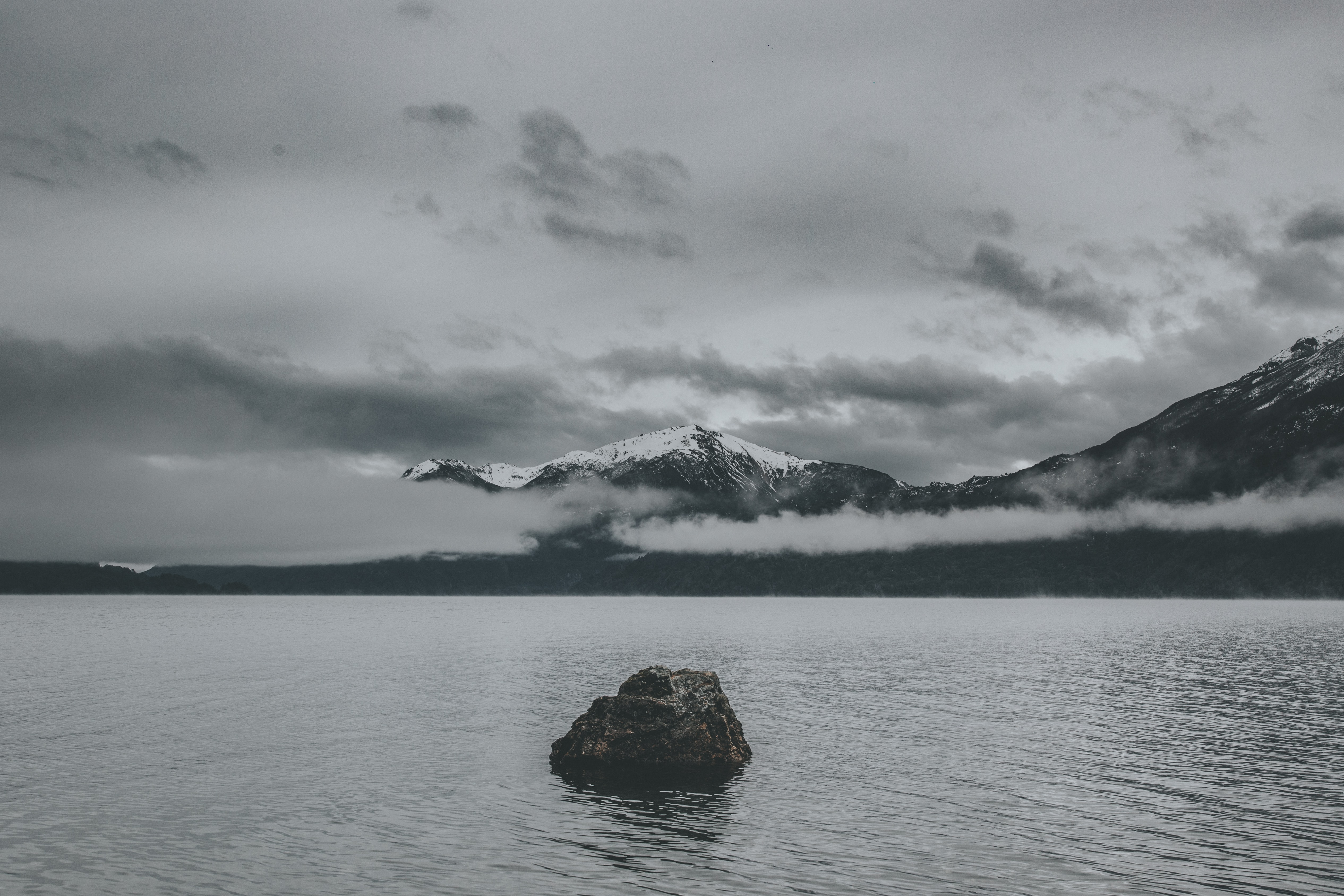 body of water near mountain under the cloudy sky