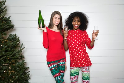 woman holding wine bottle while another woman holding two clear wine glasses stocking teams background