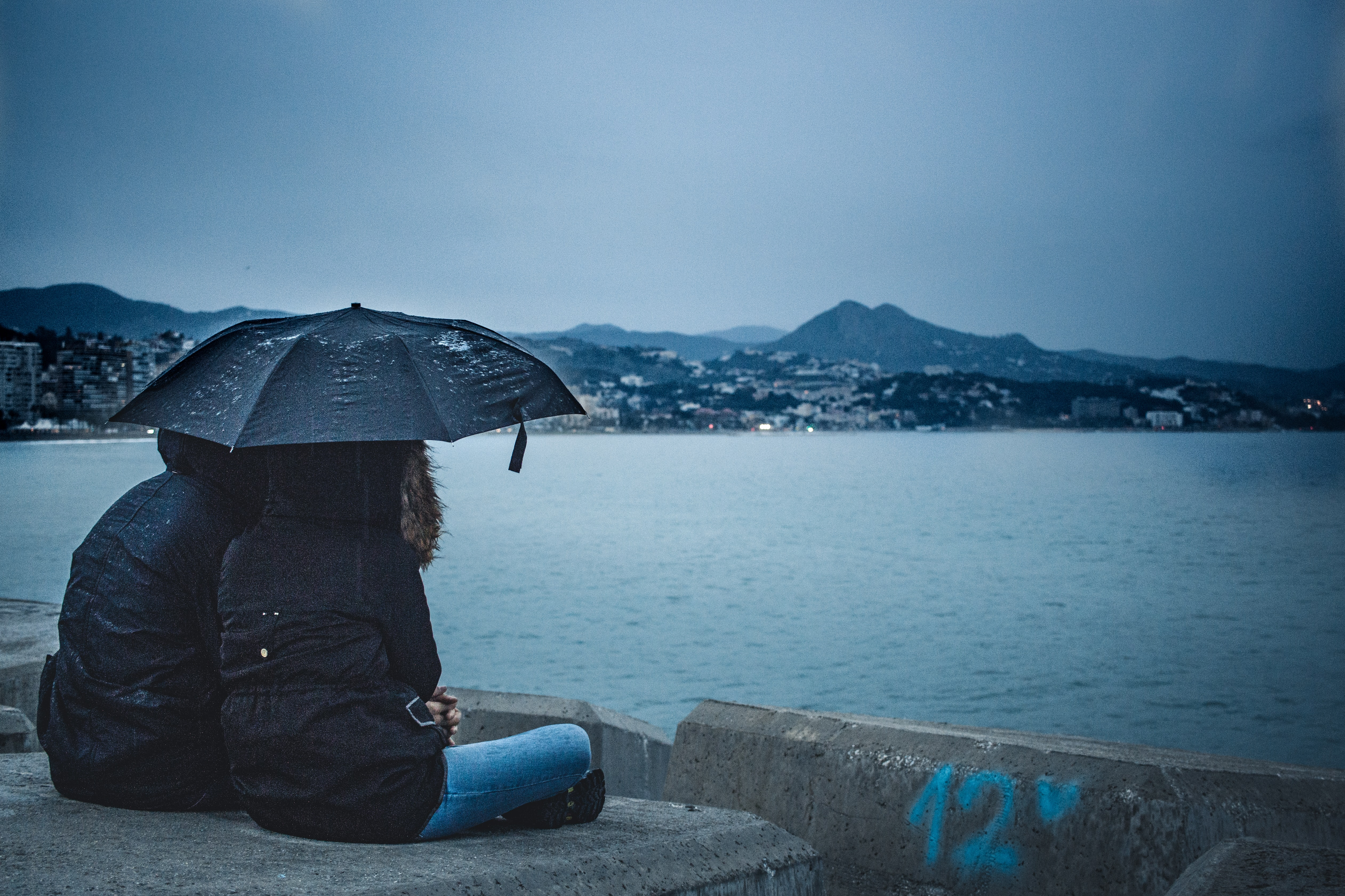couple holding black umbrella while sitting beside calm water
