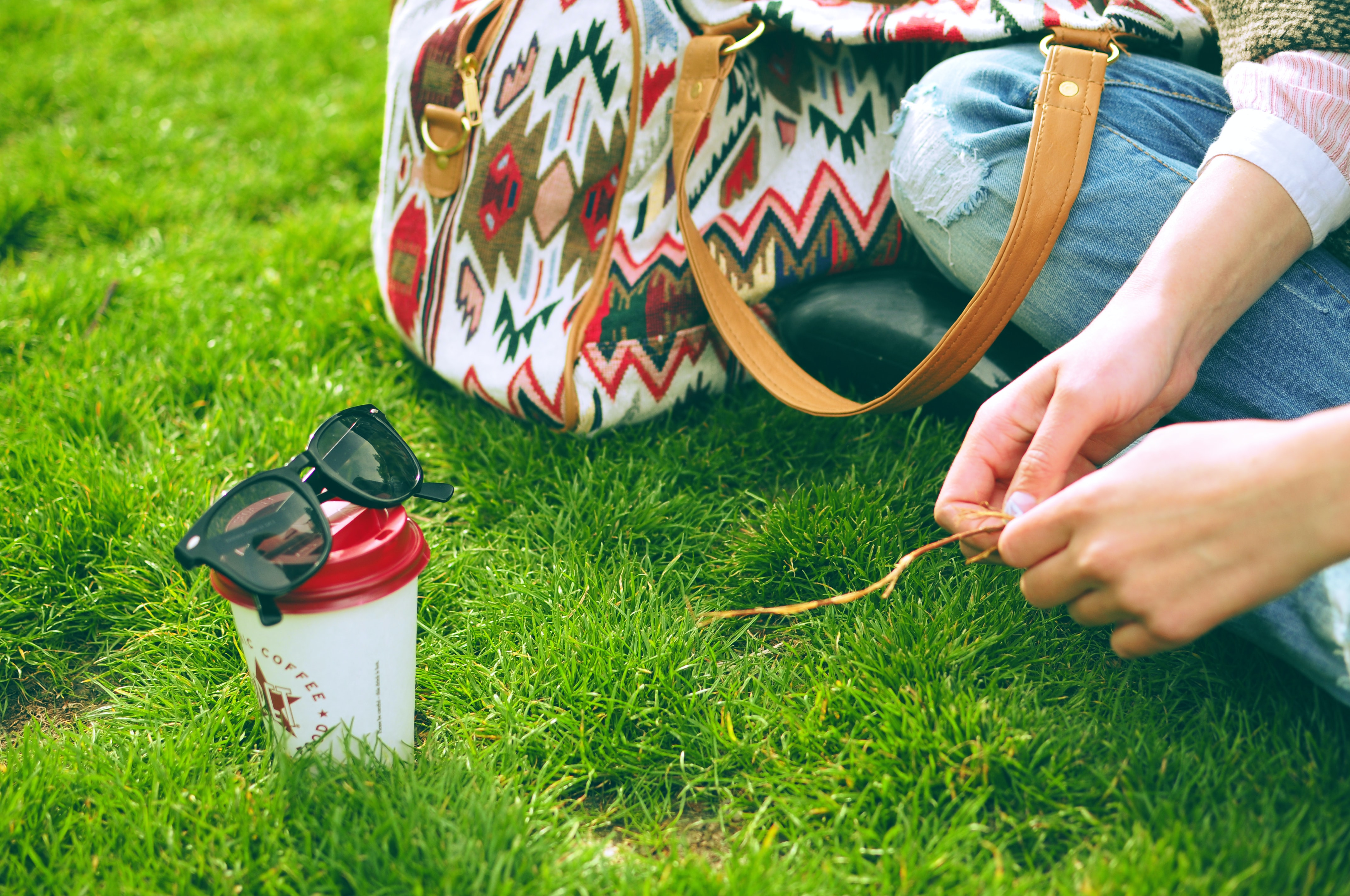 person sitting on grass near bag and cup at daytime