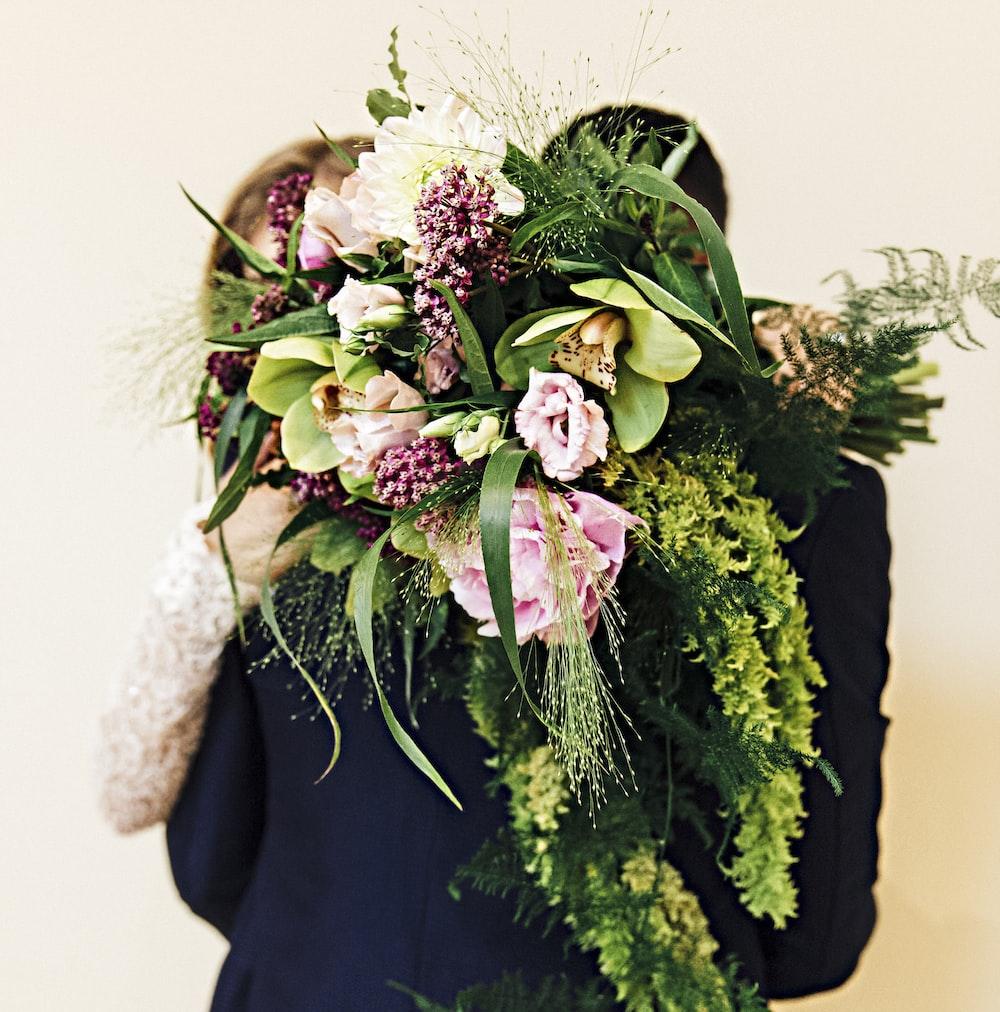 woman holding flower bouquet hugging man