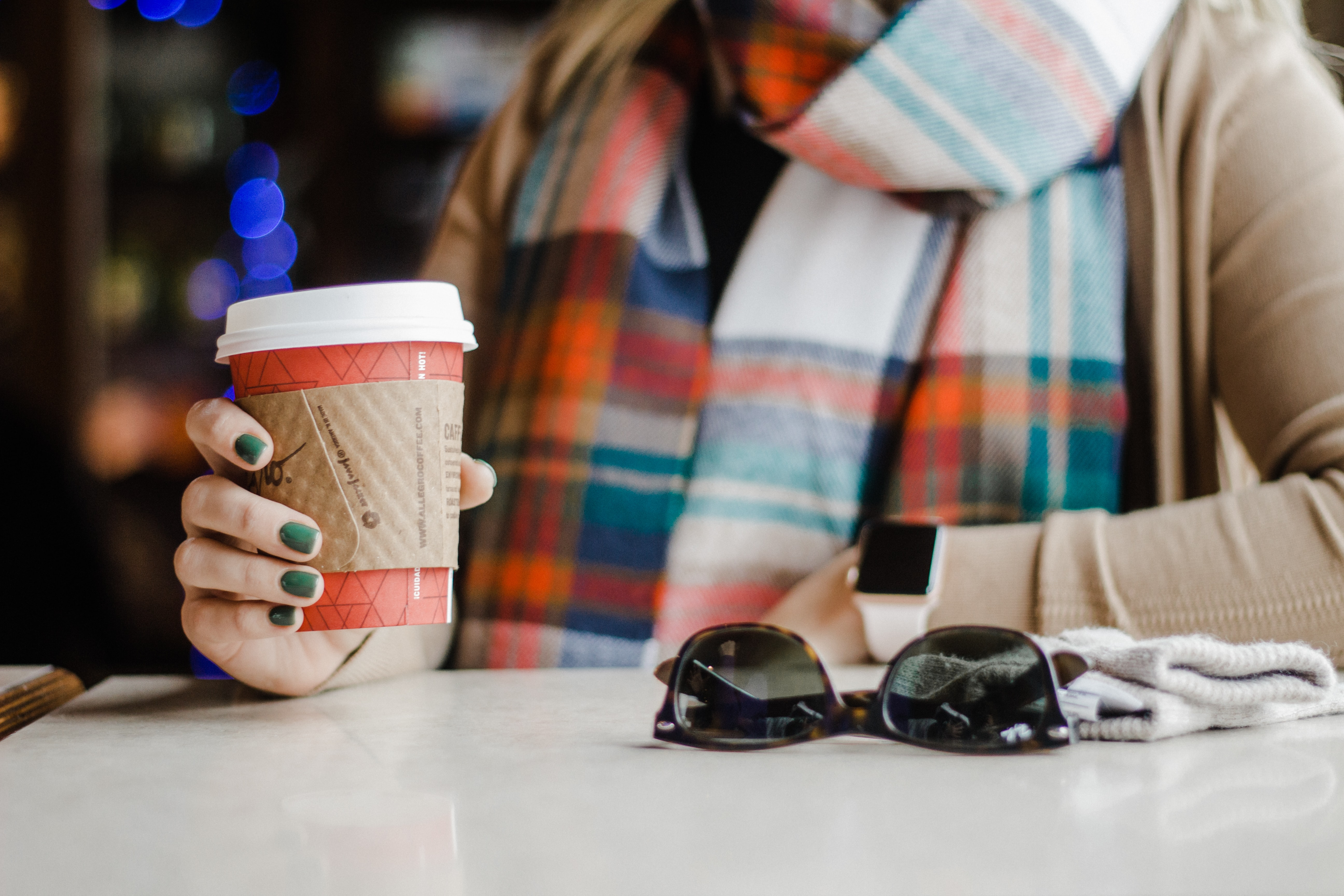 woman holding white disposable cup while leaning on table