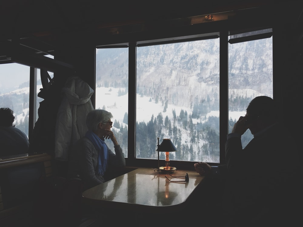 two person sitting at table watching the snow covered hill
